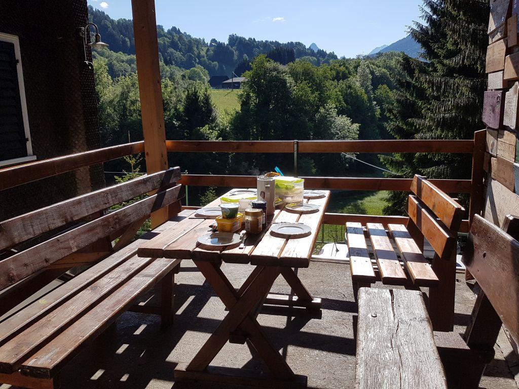 Der Frühstückstisch ist auf der Terasse am Eingang gedeckt.